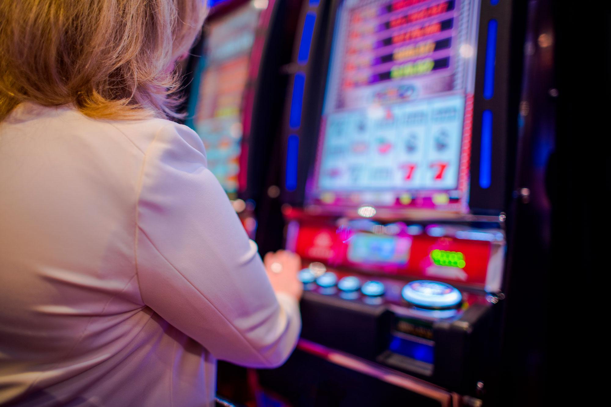Sieviete spēlē spēļu automātus.